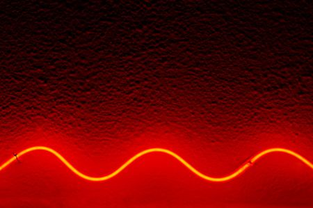 Red waved neon lamp light on stucco surface photo