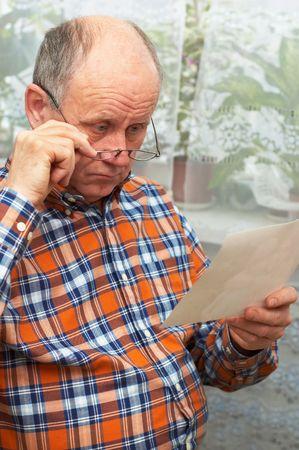 downcast: Upset casual bald senior man with glasses looks at photo. Emotional portrait series.