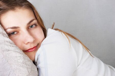 Daydreaming young girl in white lying on pillow. photo