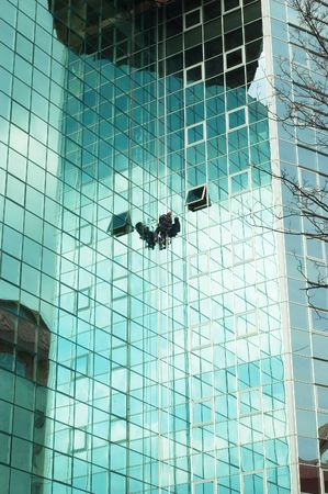 steeplejack: worker climbing at mirror wall of office building