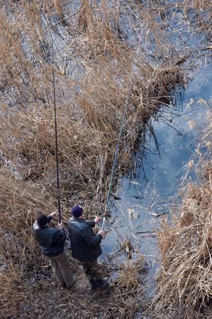rushy: Two men are fishing with rods on the rushy coast