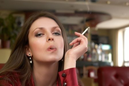 sesy green eyes brunete in red with smoking cigarette photo