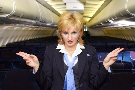air hostess: air hostess gesturing in the empty airliner cabin