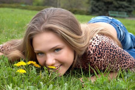smells: pretty girl smells dandelion on the green meadow