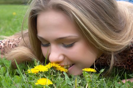 pretty girl on the meadow smells flower of dandelion