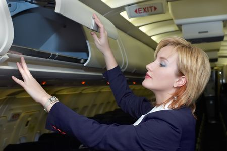 Air hostess is checking open luggage box in the cabin Stok Fotoğraf