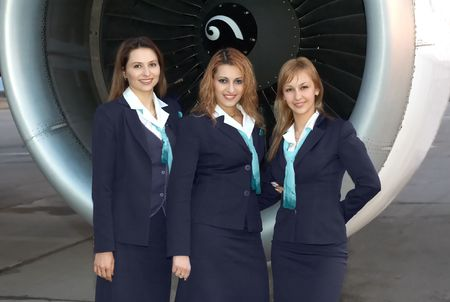 air hostess: Three beautiful stewardesses in front of aircaft engine Stock Photo