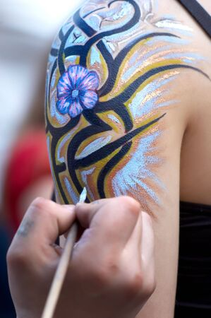 body painting in process. flourish design. selective focus. photo