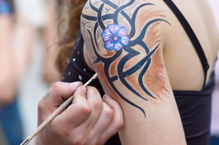 body painting in process. flourish design. selective focus. Stock Photo