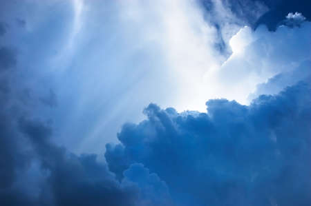 brightly: dramatic deep blue cloudscape, brightly lit in some places