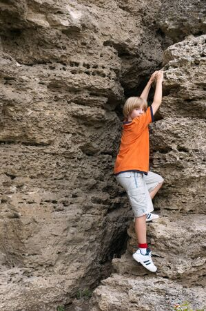 little boy in orange t-shirt climbing on rock Stok Fotoğraf
