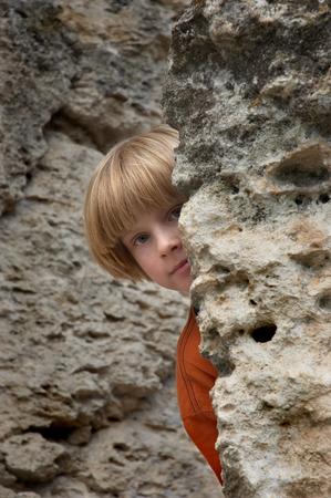 mountain peek: boy playng hide and seek game in the rocks Stock Photo