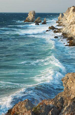 mar azul y rocas storming en la luz de la puesta del sol