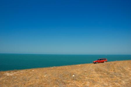 coche rojo en la pendiente en el cielo y el mar de fondo  Foto de archivo