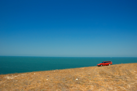 red car on the slope on the sky and sea background