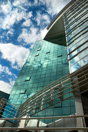 mirror-walled business center with erflection of cloudy sky photo
