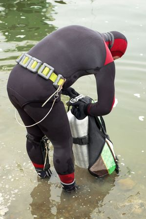 skindiver: scuba diver in wet suit preparing to enter the cold water Stock Photo