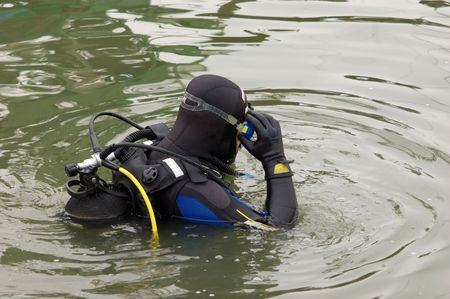skindiver: Scuba diver in wet suit entering the cold water