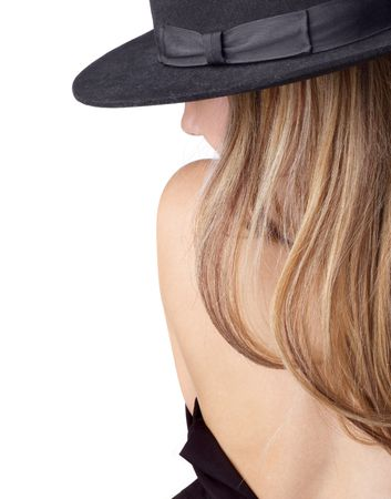 Backside view of topless and undressing blond girl in black felt hat. Isolated on white, copyspace.