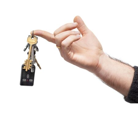 keyring: mans hand holds bunch of keys and car remote, hanging on keyring. isolated on white