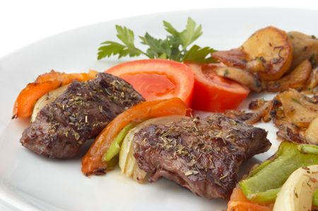 kebab served with grilled vegetables on white plate, selective focus photo