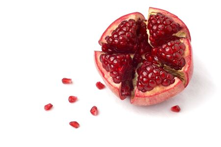 broken ripe pomegranate fruit and seeds over white cloth. isolated.