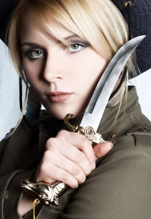 serious blond nordic girl with sharp knife in her hand