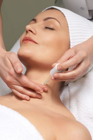 applying of anti-wrinkles treatment for neck skin in the beauty salon Stock Photo