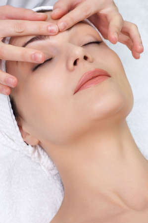 pretty woman getting facial massage in the beauty salon Stock Photo