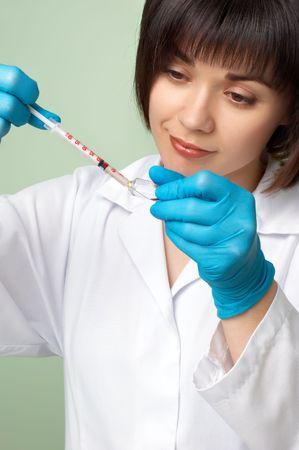 smock: brunette doctor in white smock filling the insuline syringe.