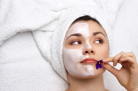 young pretty woman getting facial mask (applying is not finished yet) photo