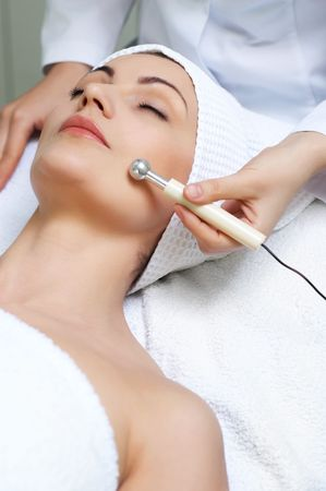 young pretty woman getting special skin treatment at beauty salon photo