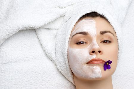 young pretty woman getting facial mask, lot of copyspace photo