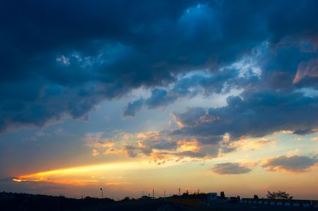 rural skyline: colorful sunset with clouds and sunbeams over rural skyline