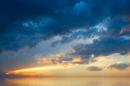 puesta del sol colorida con horizonte rural del excedente de las nubes y de los rayos de sol