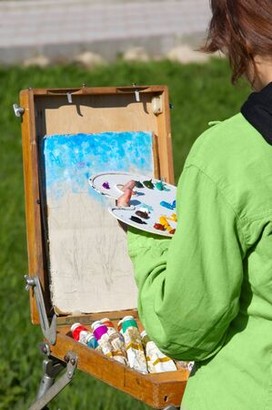 young female artist working at open air, creating oil paint. selective focus. photo