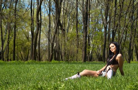 sexy brunette getting spring sunbath, sitting on the green grass photo