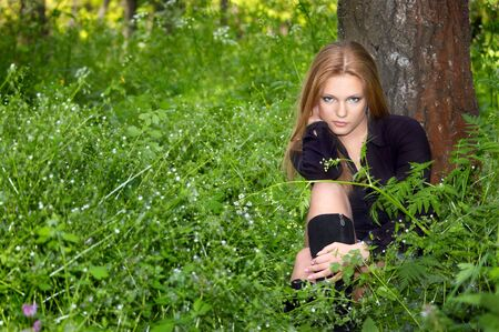 sexy girl in black boots in the green spring forest photo