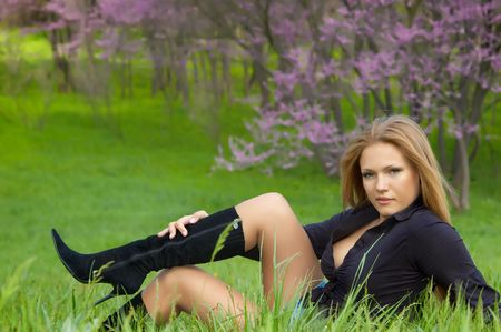 sexy girl in black boots sitting on the green grass photo