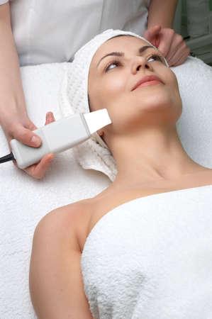 mujer que consigue la limpieza de la piel del ultrasonido en el sal�n de la belleza Foto de archivo