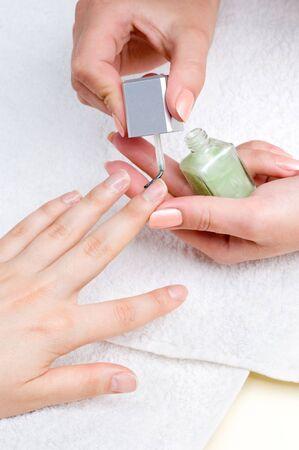 applying manicure: moisturizing the nails and skin around nails photo