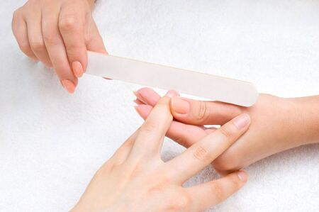 applying manicure - processing nails with emery nail-file Stock Photo - 3101027