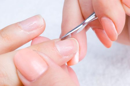 manicure applying - cleaning the cuticles with special instrument photo