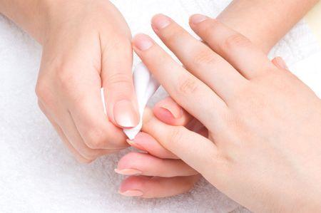 la aplicaci�n de manicura - borrar el humectante de final de los dedos