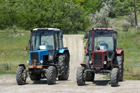 two dusty wheeled tractors at countryside, ready to work photo