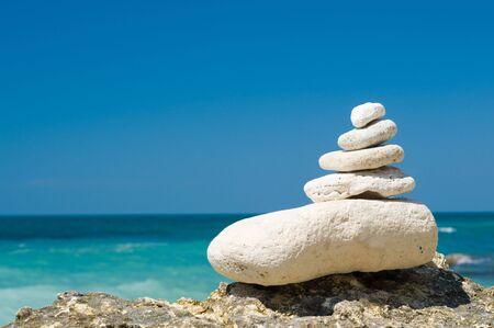 guijarros de piedra caliza apilados en la playa, fondo borroso  Foto de archivo