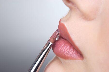 applying liquid gloss at the lips, moisturizing them photo