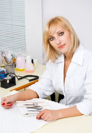 beautiful blond female manicurist portrait at work. interior of nail salon. photo