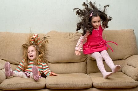 two little girls jumping on sofa, motion blur on some places Stok Fotoğraf
