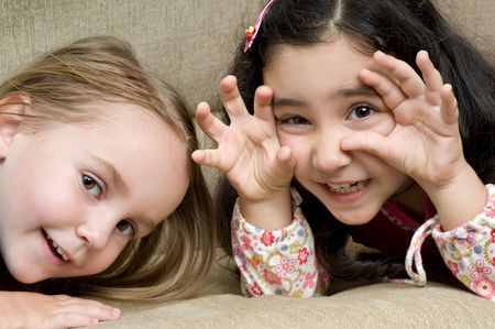 two cute little girls lying on the sofa photo